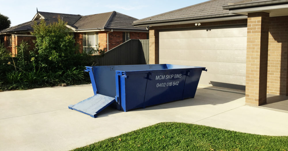 4 cubic metre skip bin with easy-load doors in driveway of home in Menai